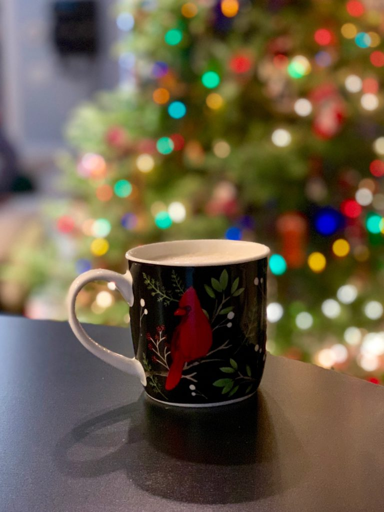 A coffee mug with a cardinal on it in front of a Christmas tree.